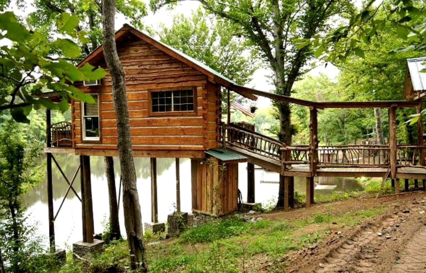 Tree house for rent with elevated walkway on a body of water in Jackson, Georgia.