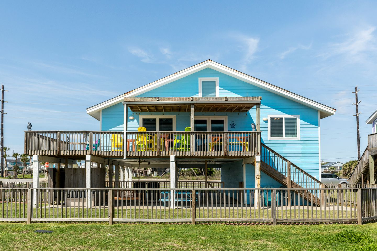 Galveston beach house rental with elevated deck and blue paneling.