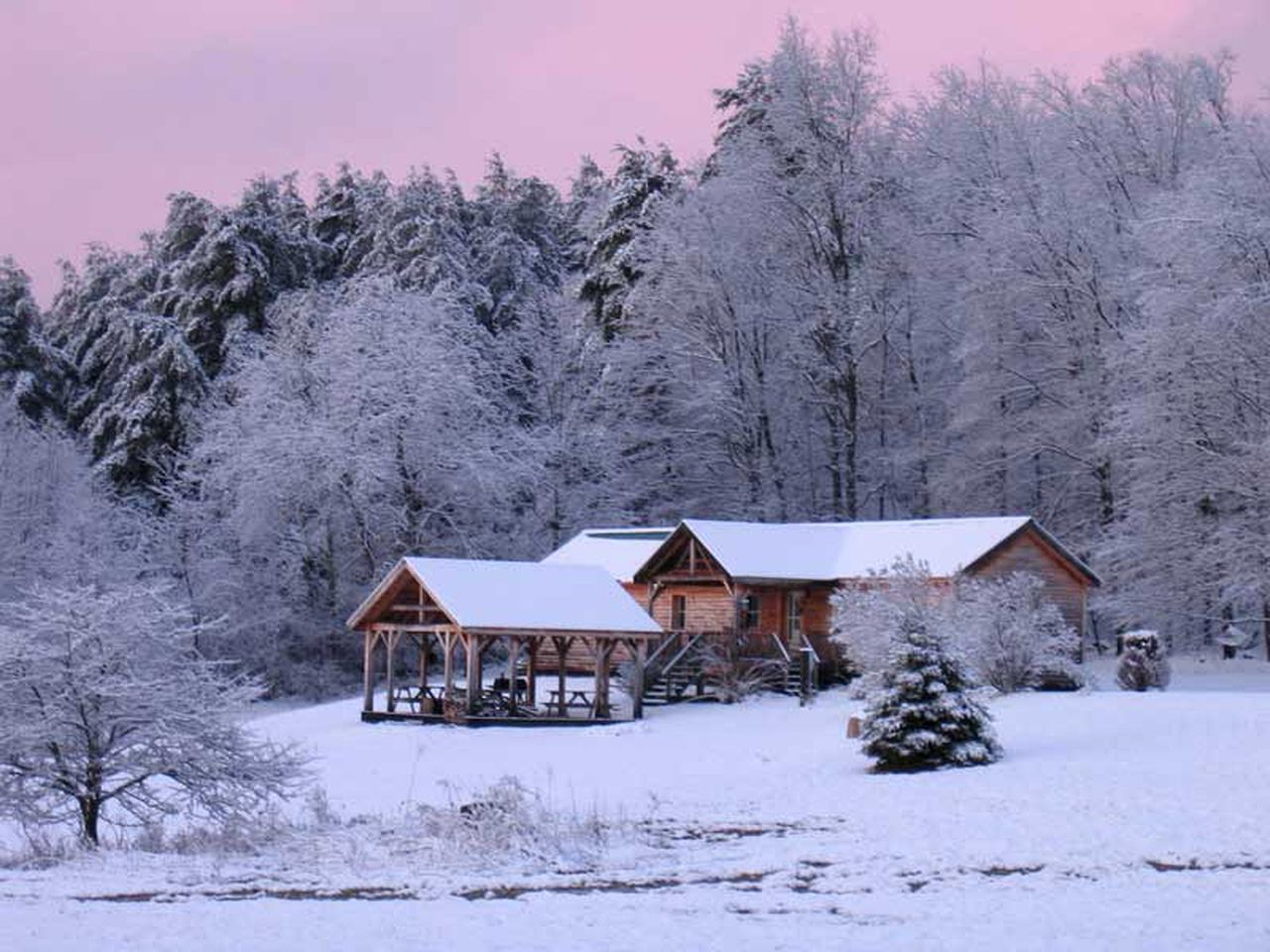 Private cabin in open field covered in snow in Upstate New York.