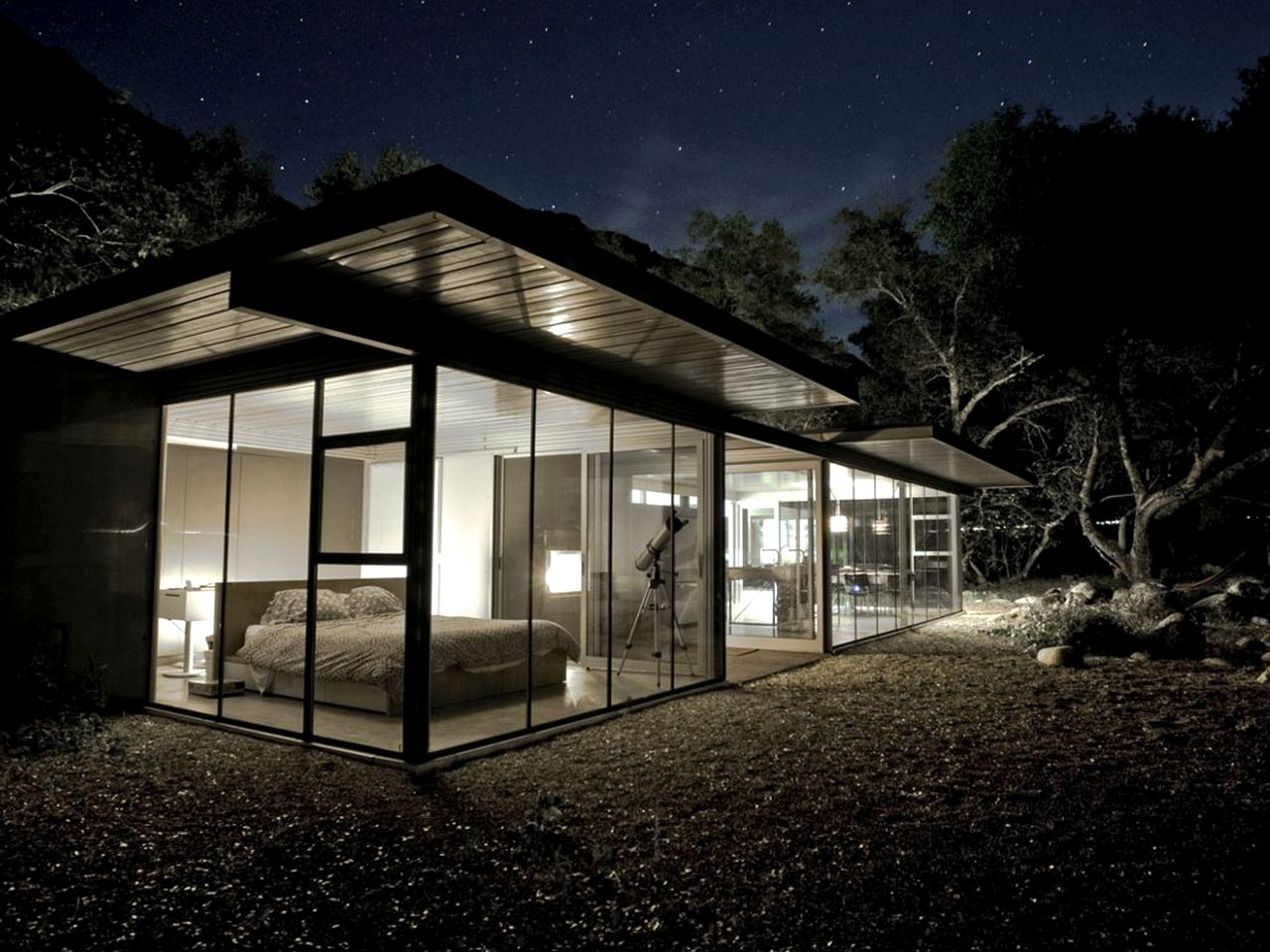 Exterior of a modern, glass house at night, with all the lights on and visible inside in California.