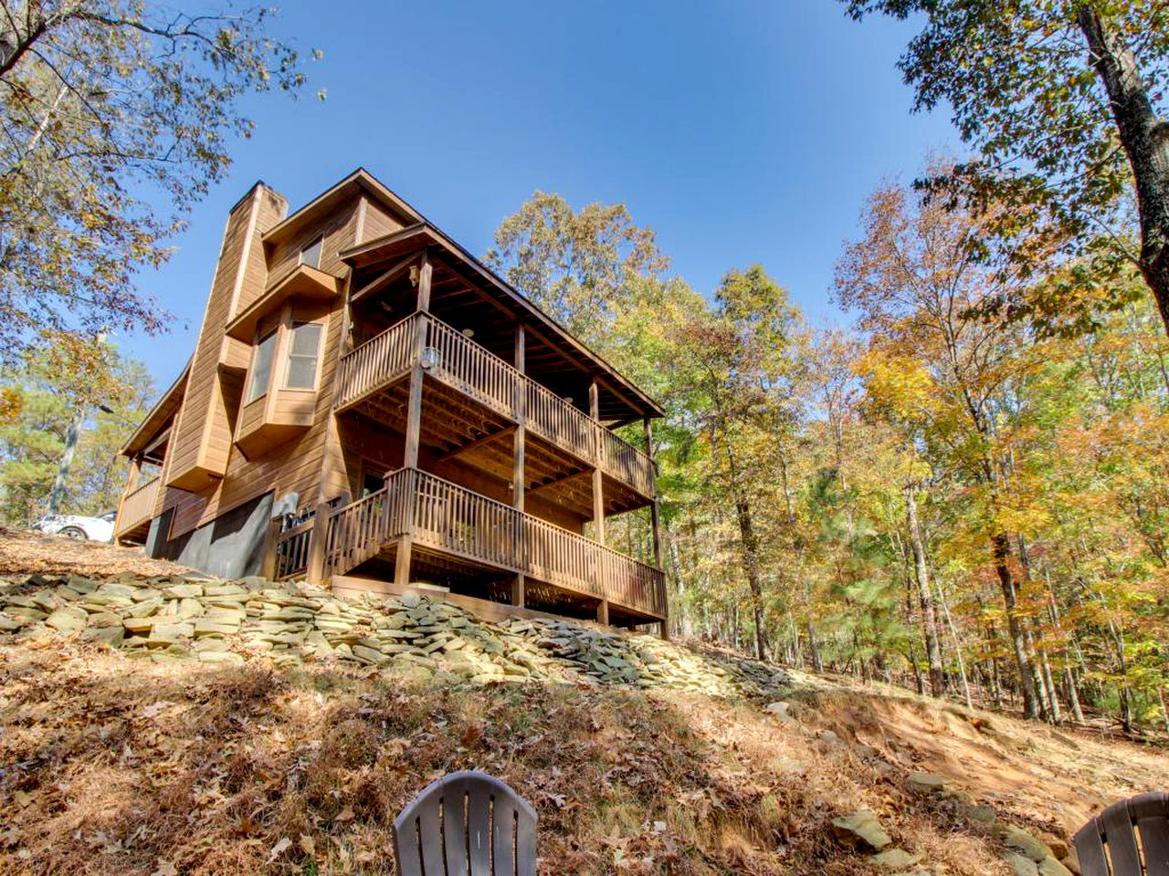 Three-story log cabin rental surrounded by trees in autumn in Ellijay, Georgia.