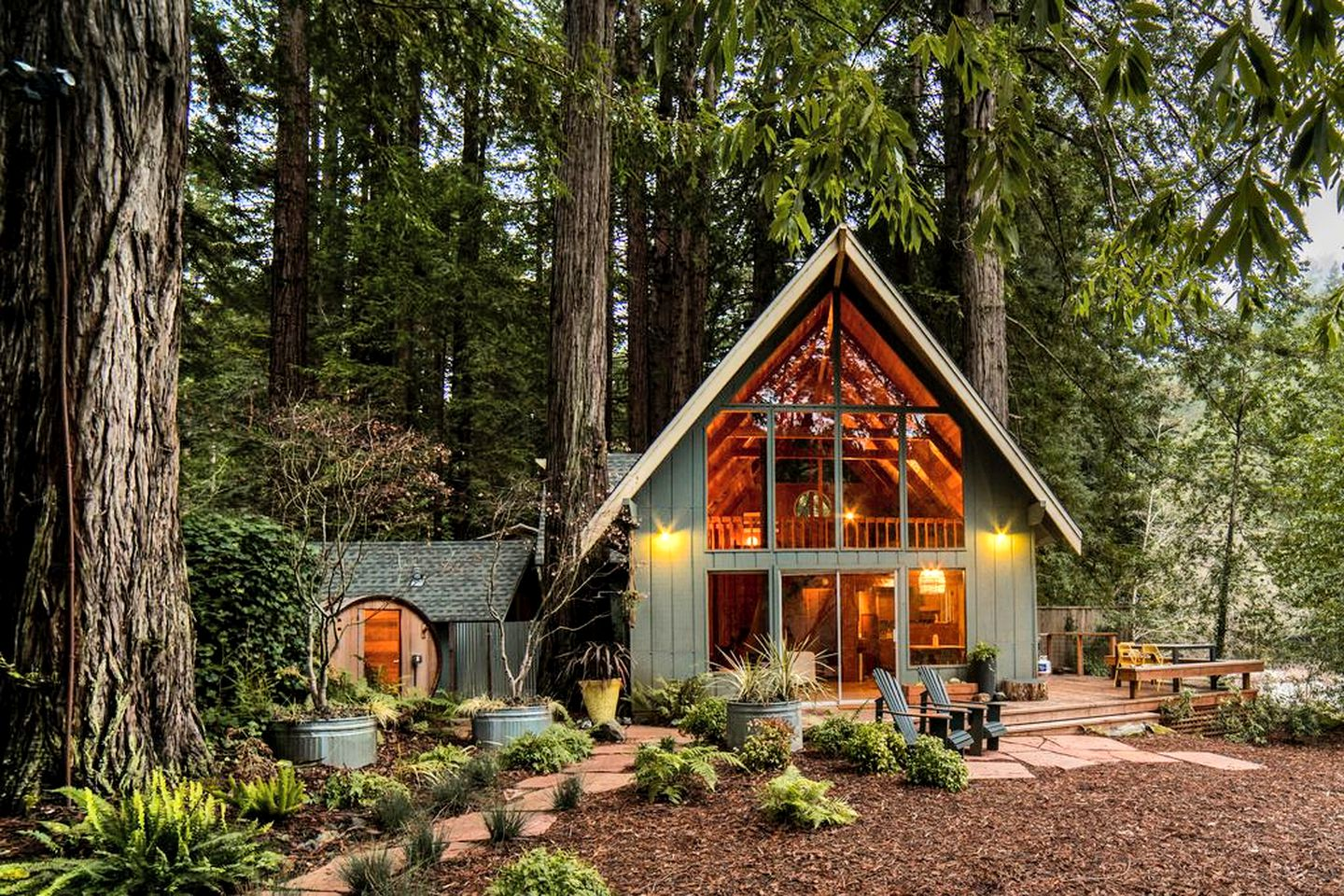 Charming California cabin rental overlooking Austin Creek in California with big glass pane exterior with lighting and deck chairs outside.