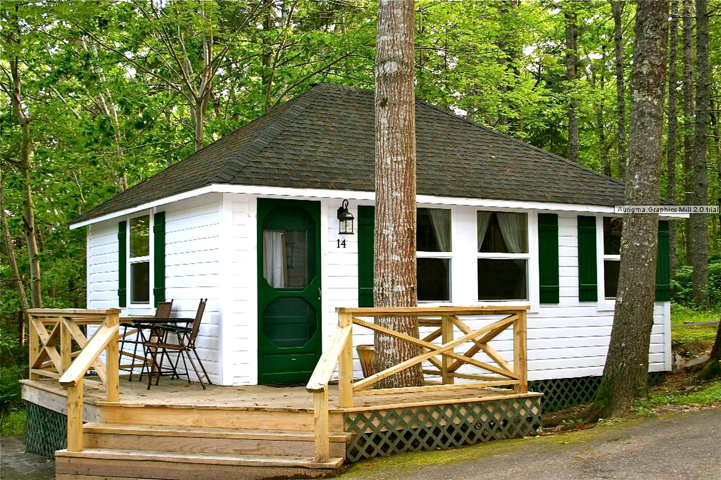 White cottage for rent surrounded by trees near the beach in Bar Harbor, Maine.