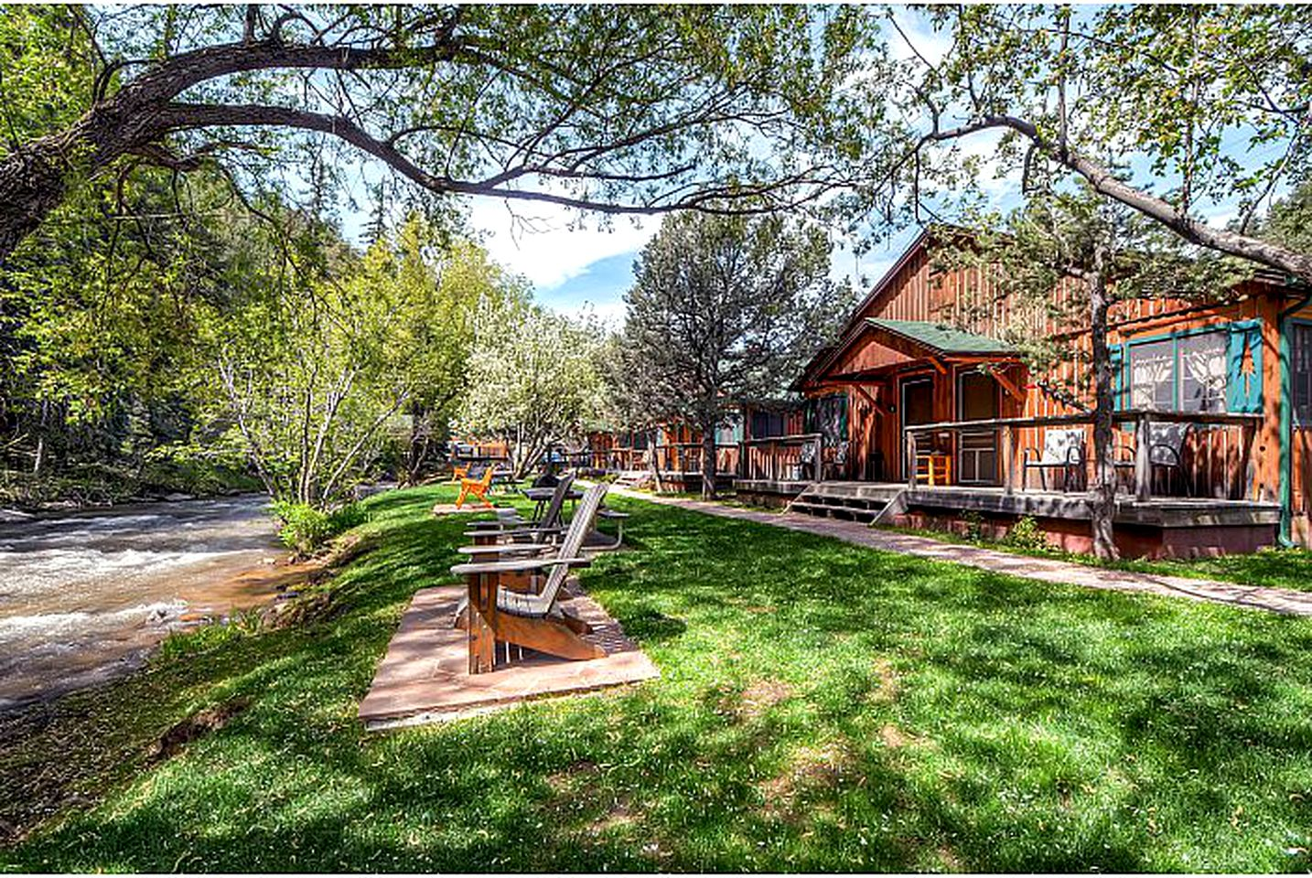 Cabins in Evergreen, CO with green grass overlooking a creek.