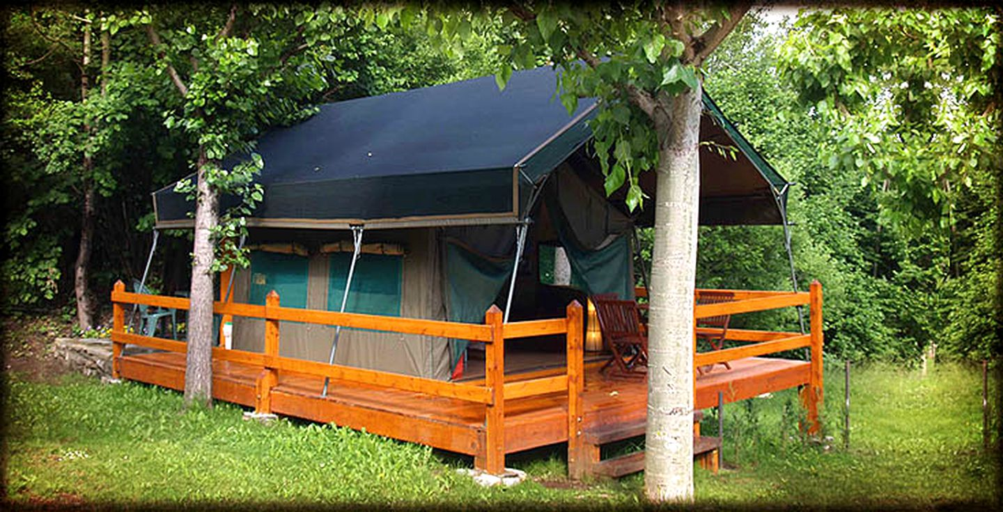 Safari tent with black roof cover, orange-brown decking with chairs, and surrounding trees all on grass.