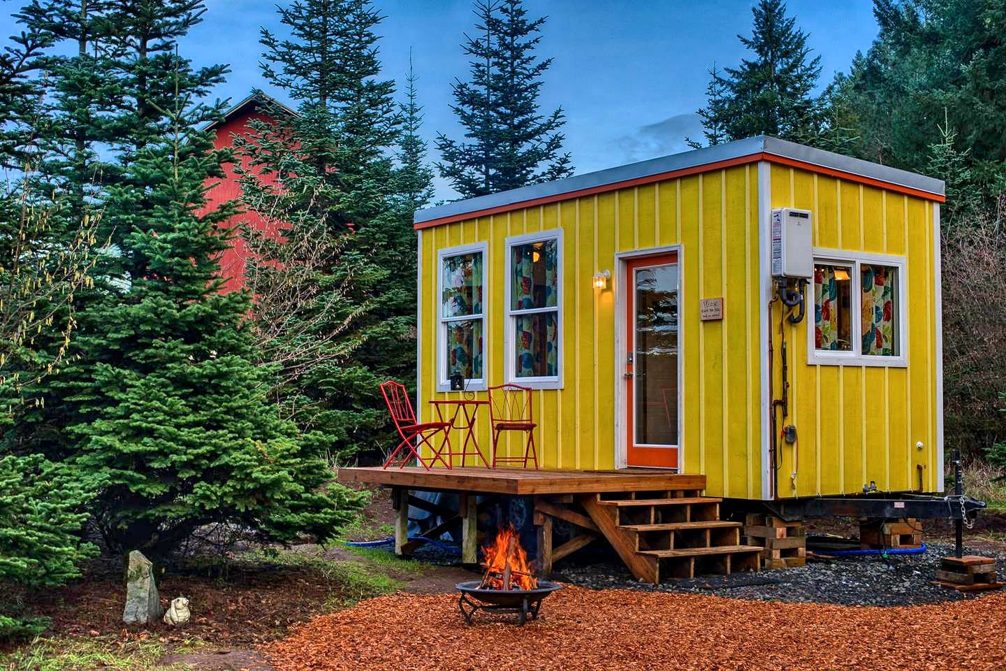 Bright yellow tiny house rental in a forest clearing near Sherwood, Oregon.