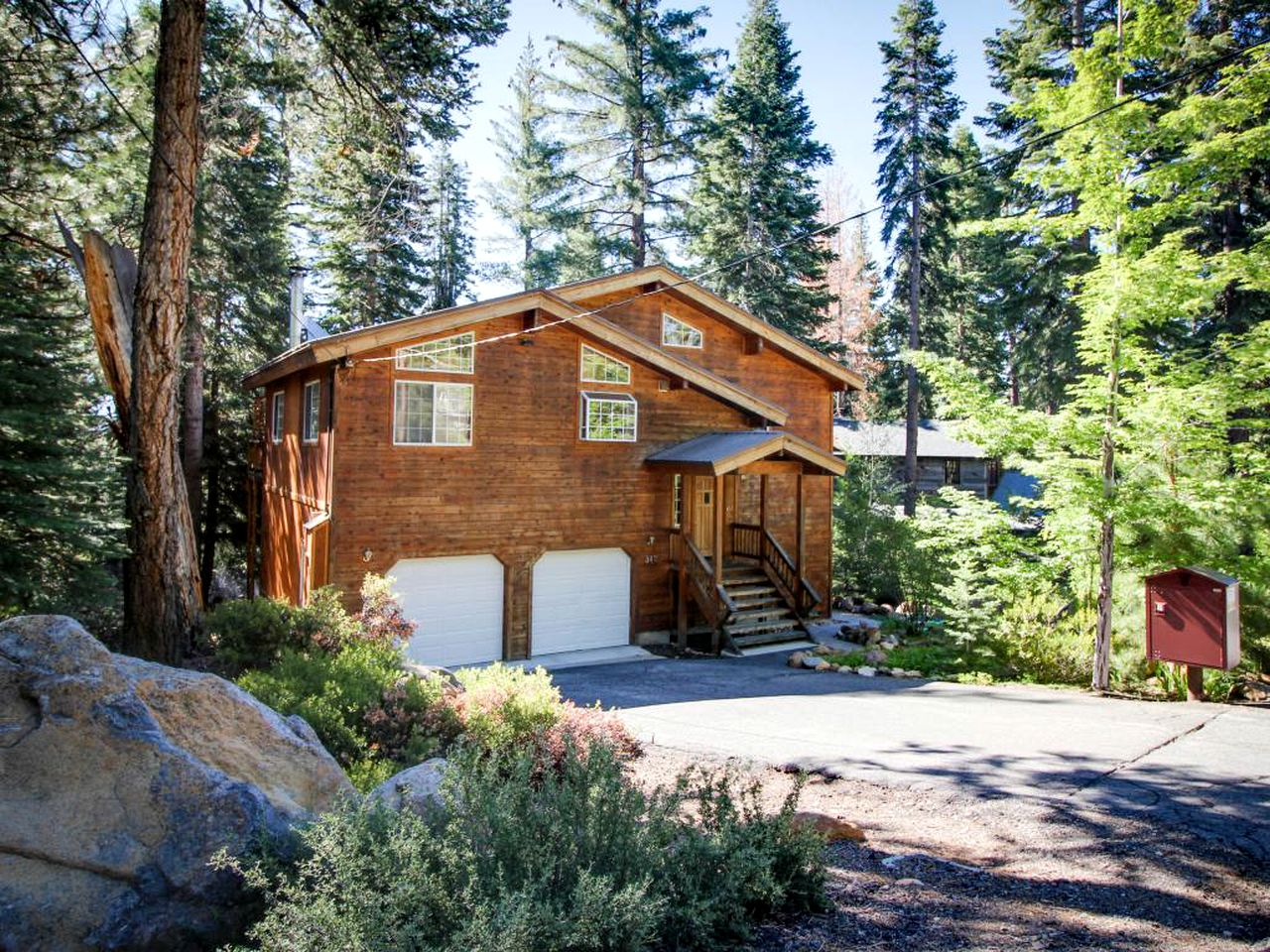 Cabin rental with two car garage surrounded by trees in Tahoe Vista, California.