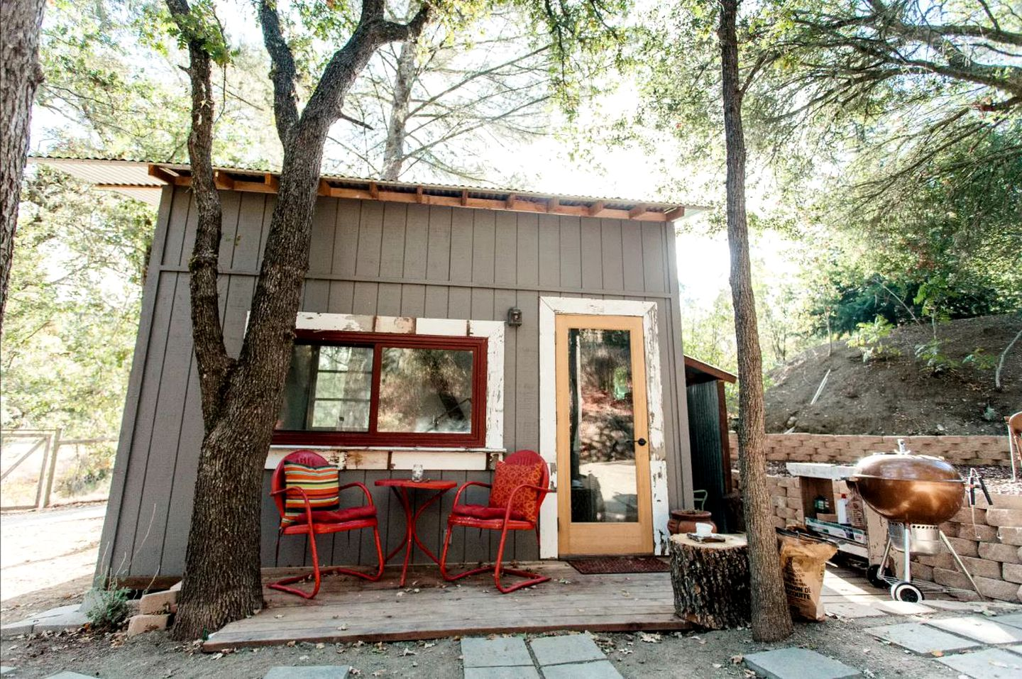 Rustic tiny house for rent surrounded by trees on a farm in Atascadero, California.