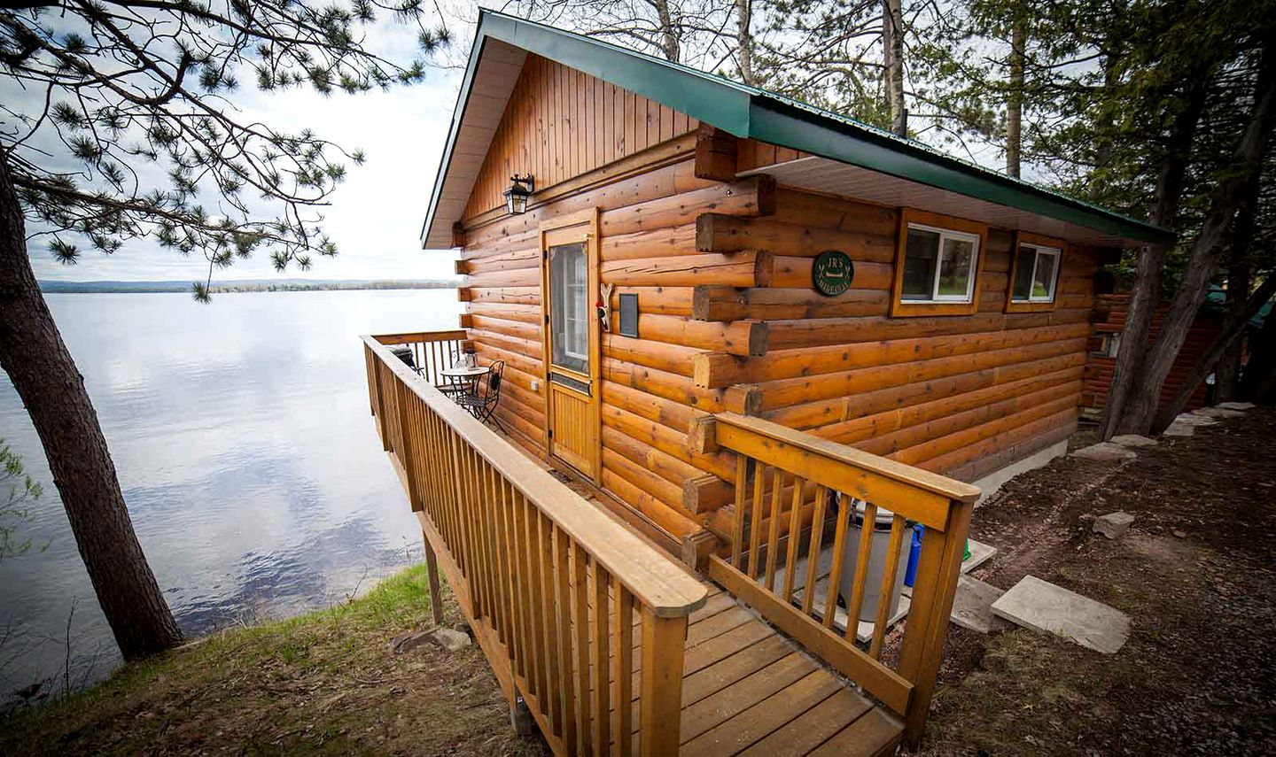 Secluded log cabin stands next to peaceful lake, the perfect day for glamping (Ontario)