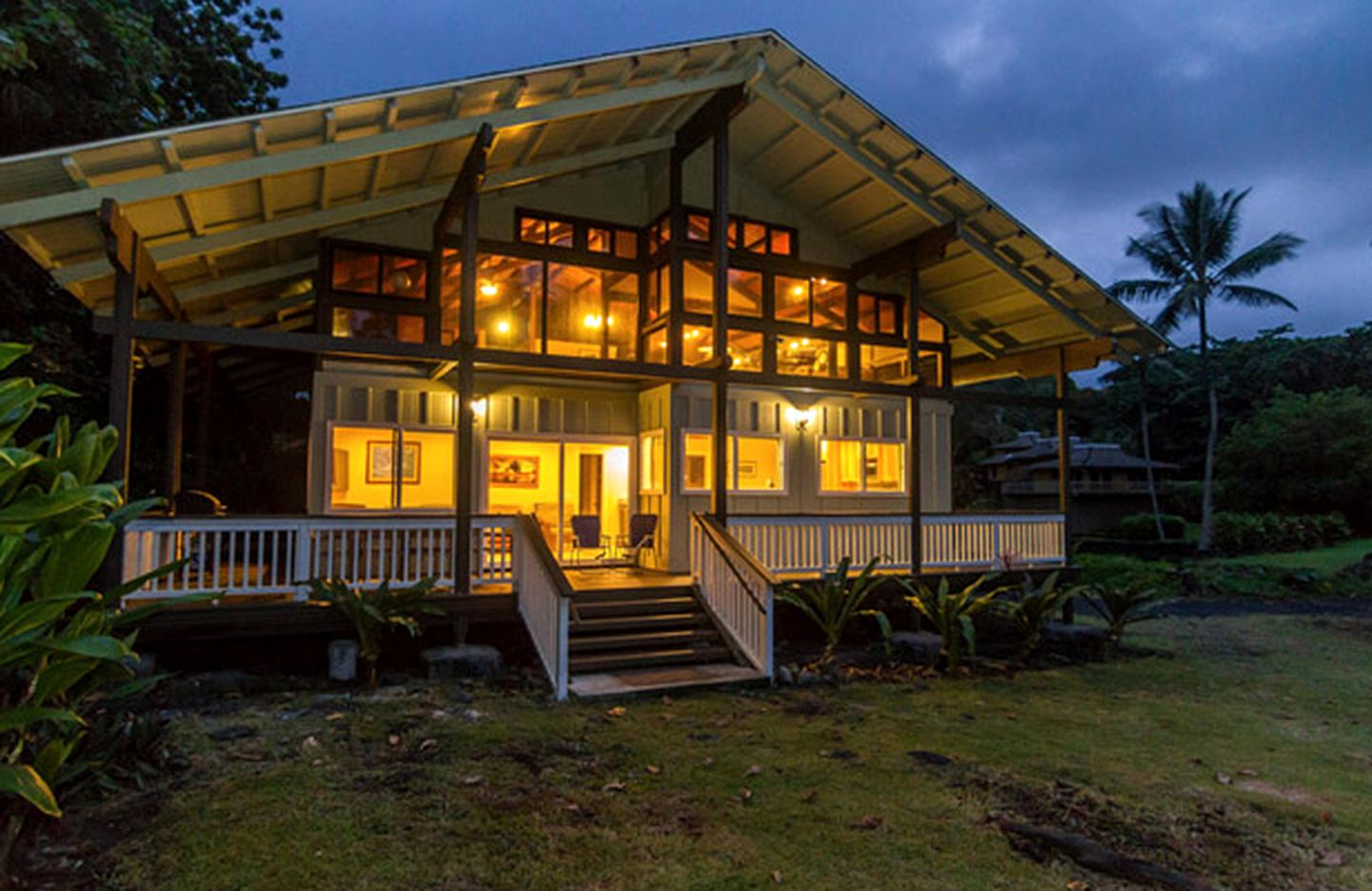 Luxury Maui cottage at night with wrap-around deck for Hawaii beach vacation.