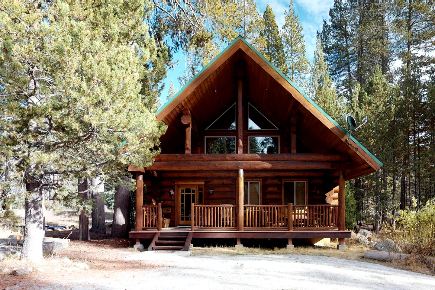 A-frame log cabin surrounded by pine trees in Lakeshore, CA.