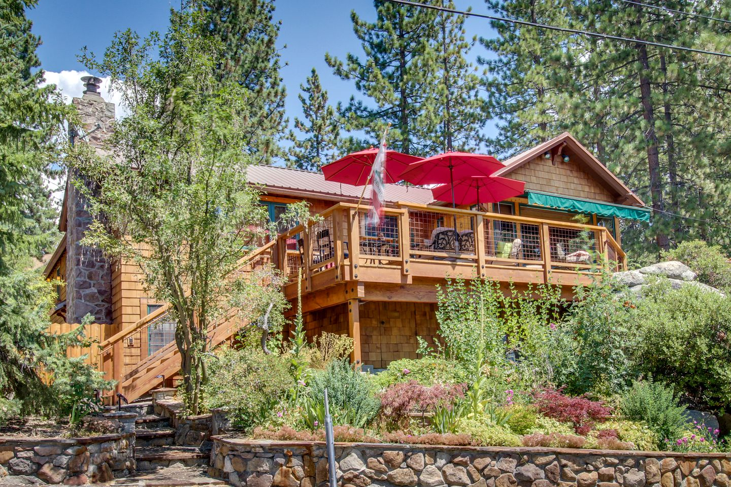 View from the water of a two-story cabin rental with elevated deck in Kings Beach, California.