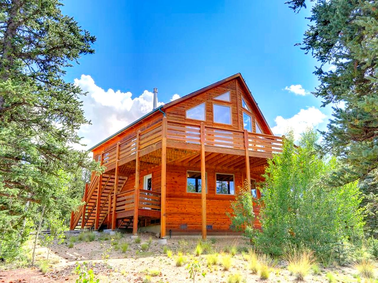 Two-story log cabin rental surrounded by trees in the Rocky Mountains near Jefferson, Colorado.