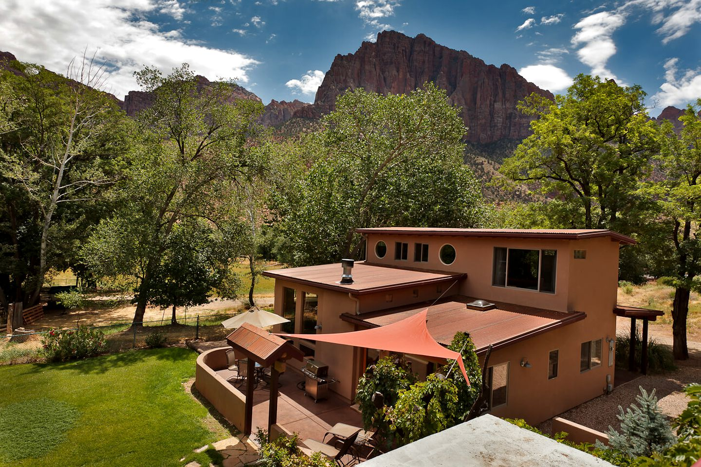 Villa rental surrounded by trees with rock cliffs in the distance in Zion Canyon, Utah.