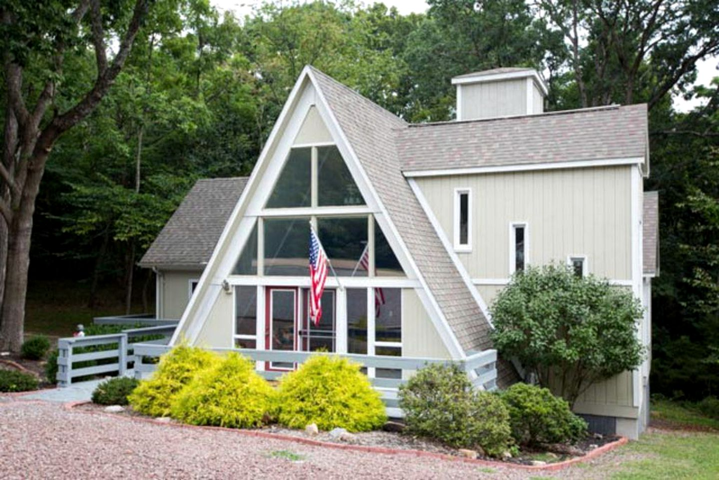 A-frame cabin rental with stone driveway and American flag hanging outside in Massanutten, Virginia.