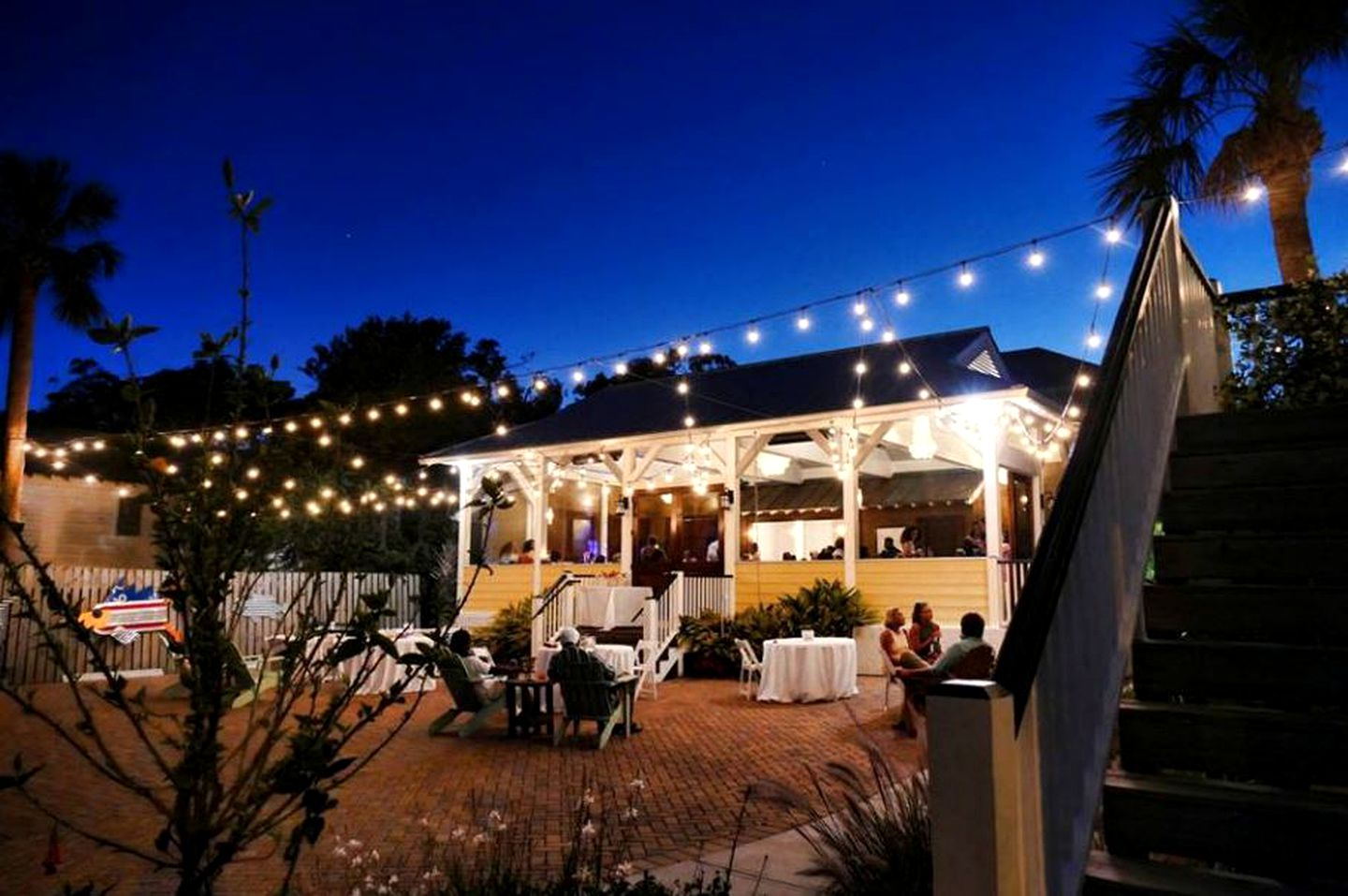 Outdoor patio at night with couples seated at tables and string lights on overhead on Tybee Island.