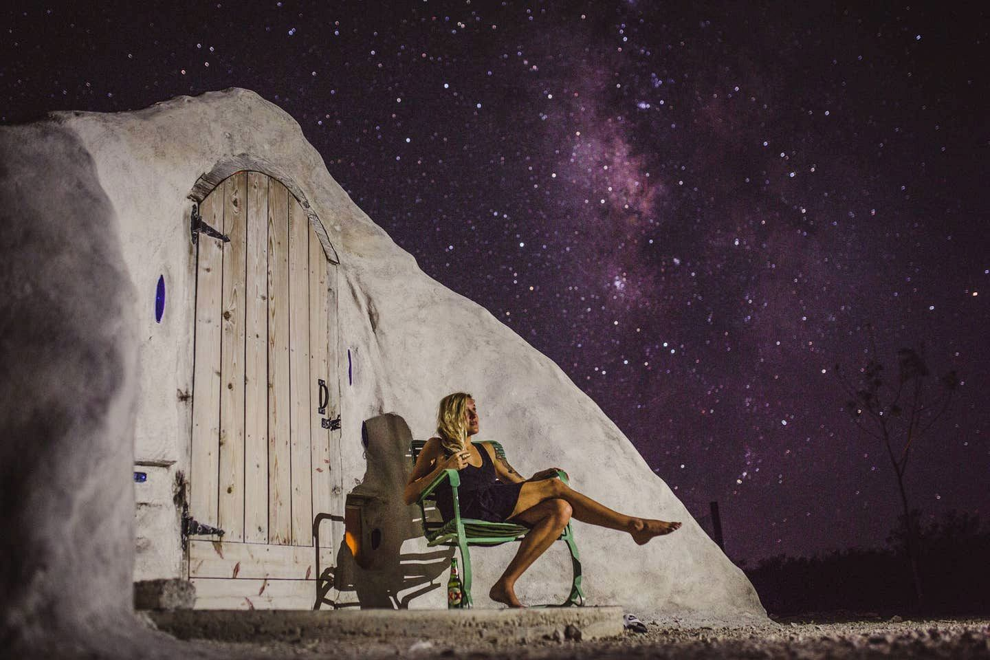 woman sat outside Texas adobe dome perfect for glamping, TX