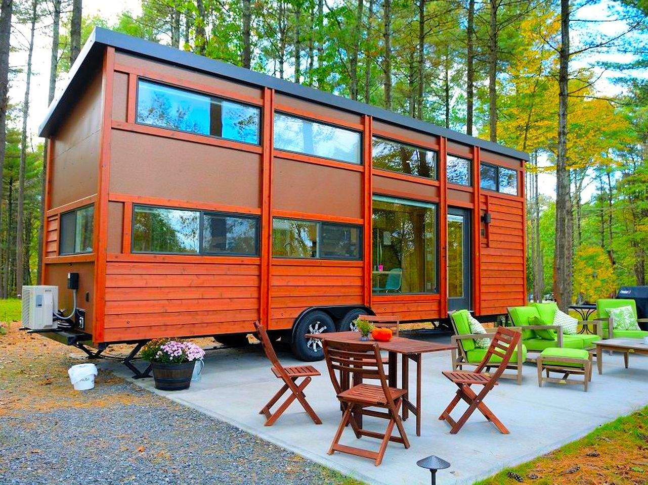 Wooden tiny house with lots of windows and patio area furnished with tables and chairs in South Cairo, New York.