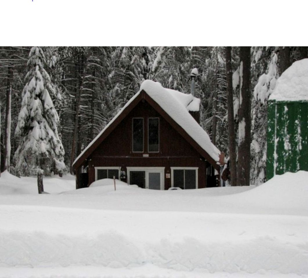 A-frame cabin rental surrounded by pine trees and covered in snow in California.
