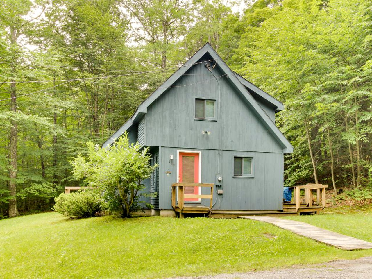 Blue cabin rental surrounded by trees in West Dover, Vermont.