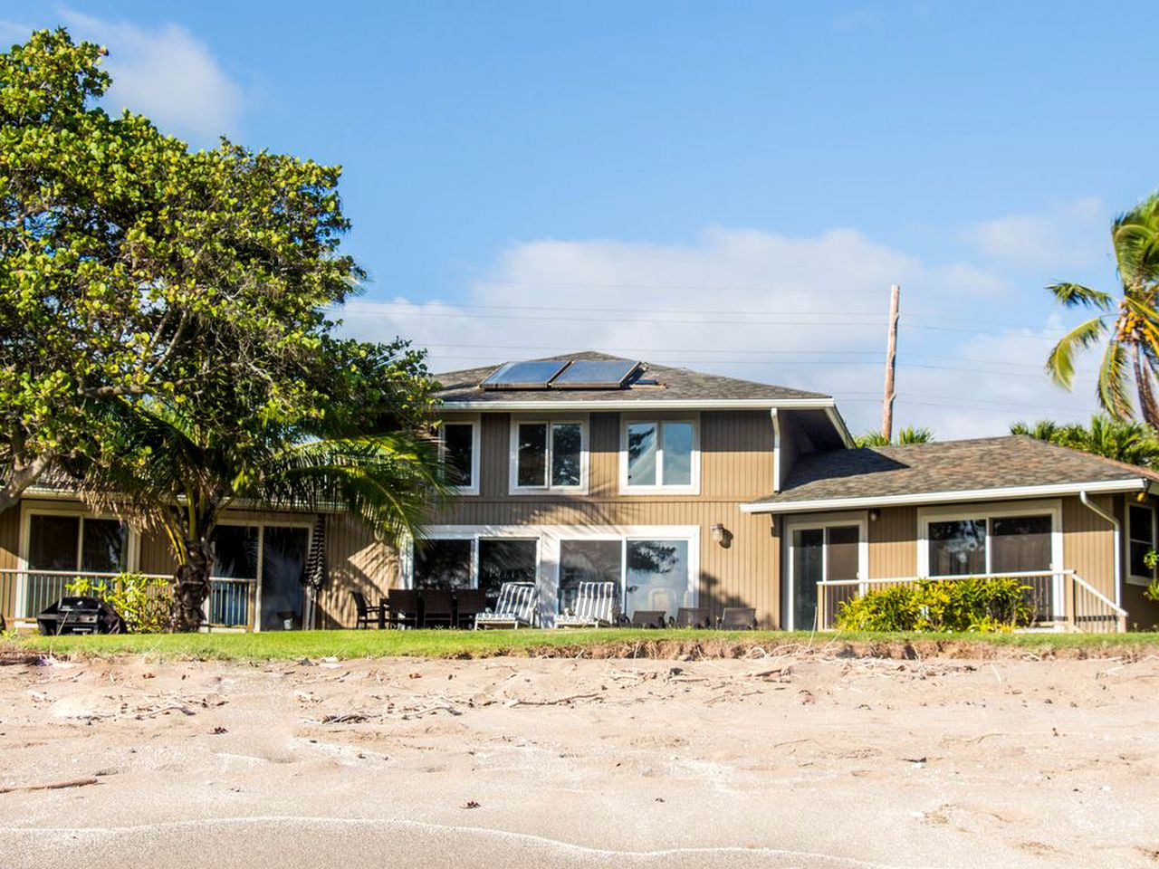View from the beach of a Kekaha beach house with a tree and grass leading to the sand.