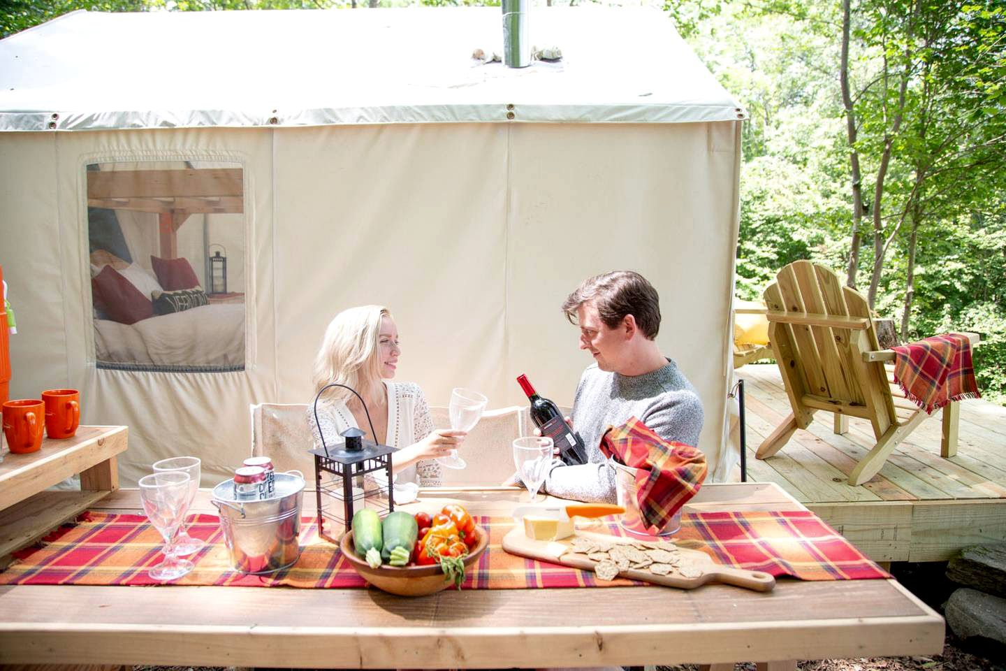 Guests enjoy a glass of wine outside luxury camping near Woodstock, VT