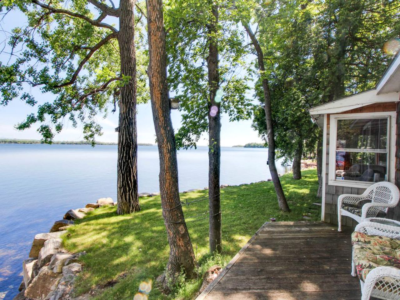 Waterfront cottage rental with front deck and porch chairs looking out over the water of Vermont'sLake Champlain.
