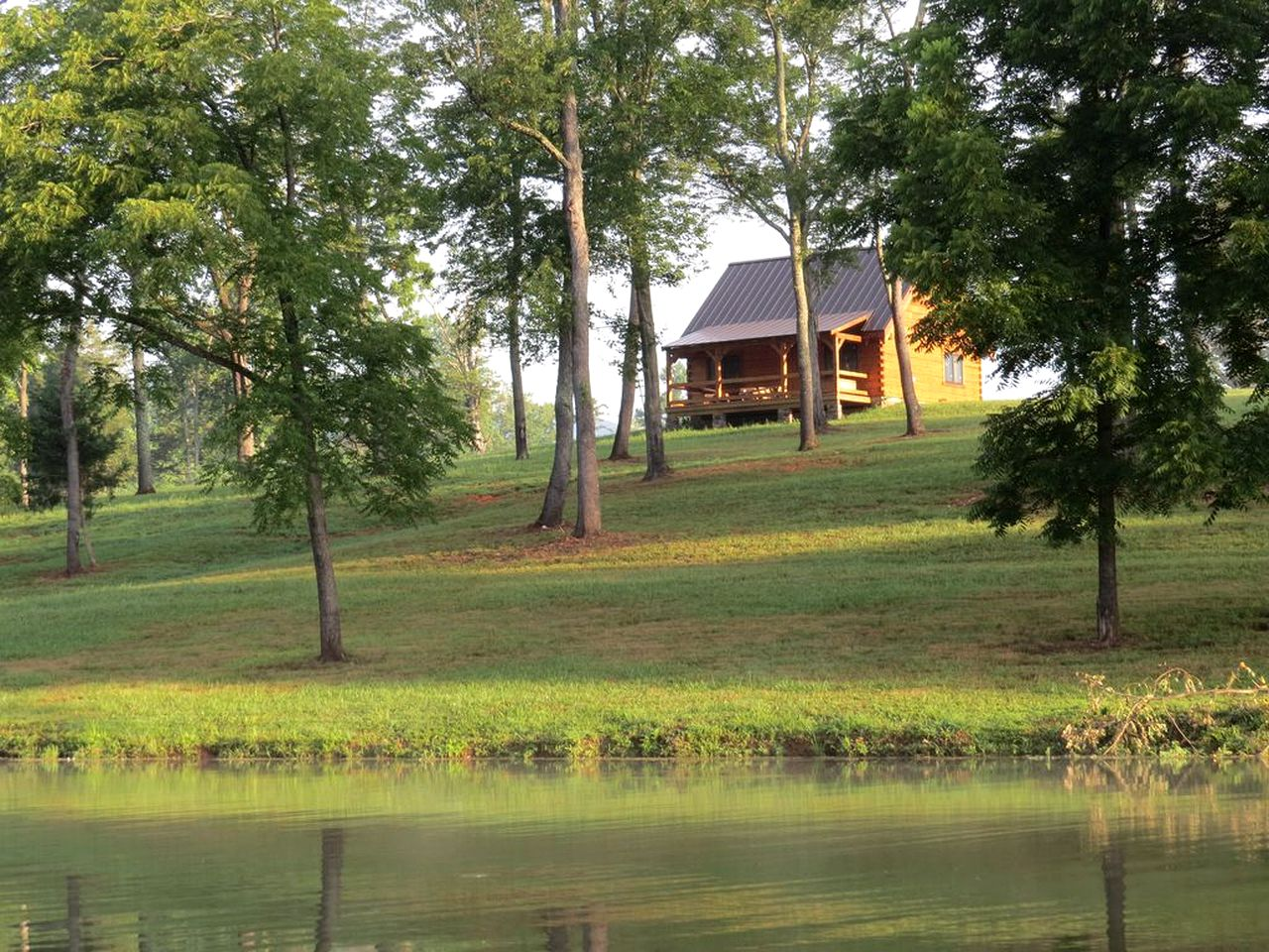 Log cabin sitting on top of hill with water bank and green forested area in front near Woods Mill in Virginia