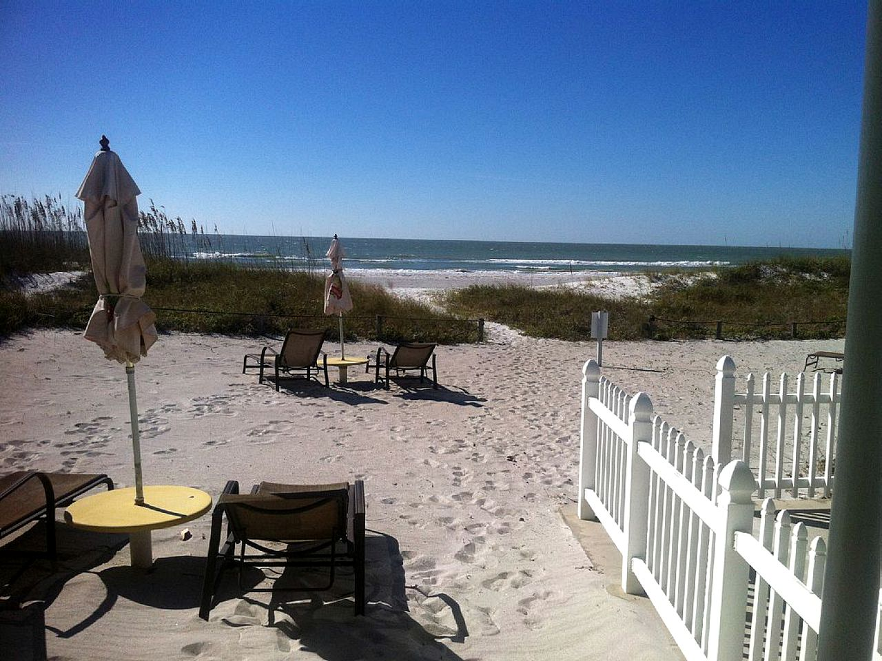 View from vacation rental on beach in Florida overlooking sand dunes and the water.