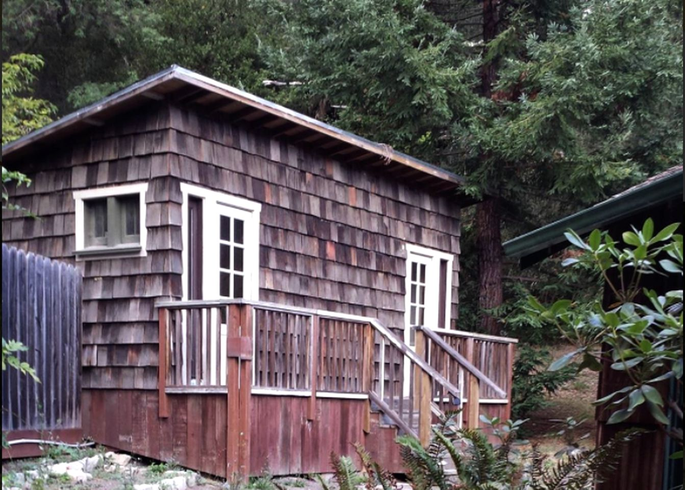 Shingled cabin rental surrounded by pine trees near the Big Basin Redwoods State Park in California.