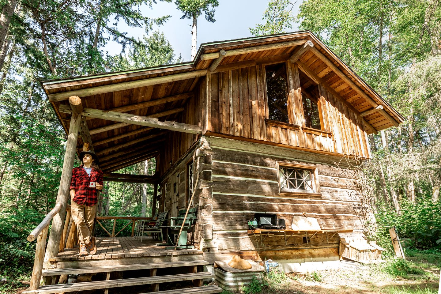 Man drinking a coffee standing on the front porch of a log cabin surrounded by forest.