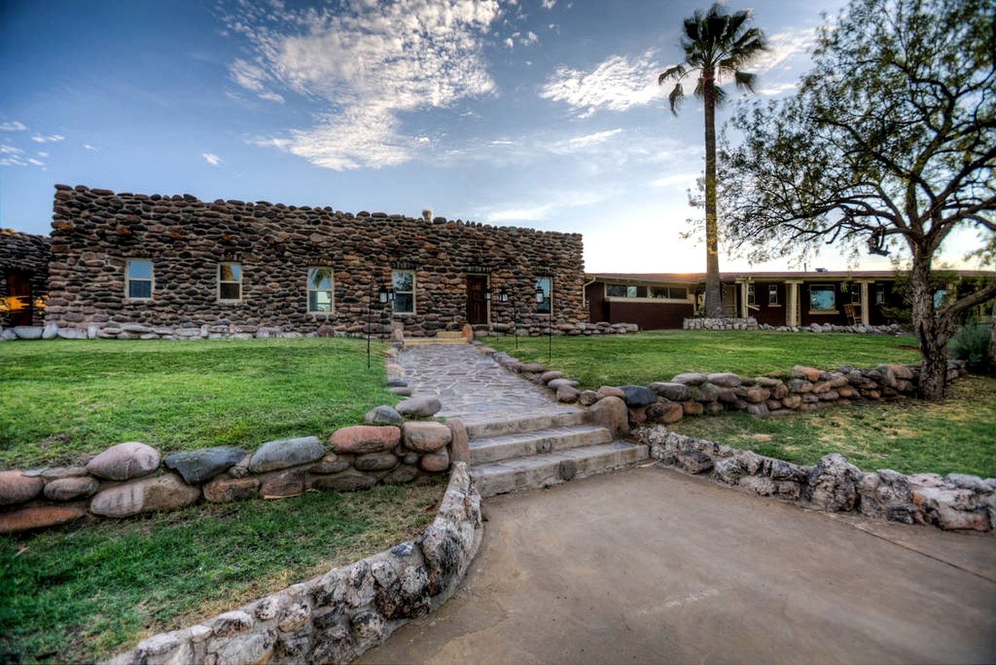 Entryway leading to stone cottage surrounded by palm trees and grass near Phoenix, Arizona.